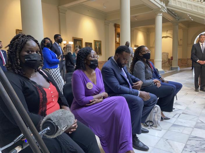 Relatives of Ahmaud Arbery including sister Jasmine Arbery (left) and mother Wanda Cooper Jones (second from left) sit at the Georgia state capitol in Atlanta on Monday, May 10, 2021. They witnessed Georgia Gov. Brian Kemp sign a law repealing citizen's arrest in Georgia, partly blamed for Ahmaud Arbery's fatal shooting death near Brunswick in 2020. (AP Photo/Jeff Amy)