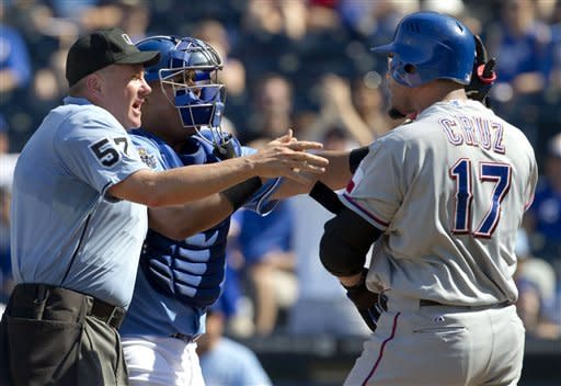 Home plate umpire Mike Everitt (57) steps between Kansas City Royals catcher Brayan Pena and Texas Rangers' Nelson Cruz (17) during the eighth inning of a baseball game at Kauffman Stadium in Kansas City, Mo., Monday, Sept. 3, 2012. Cruz was hit by a pitch on the play. (AP Photo/Orlin Wagner)