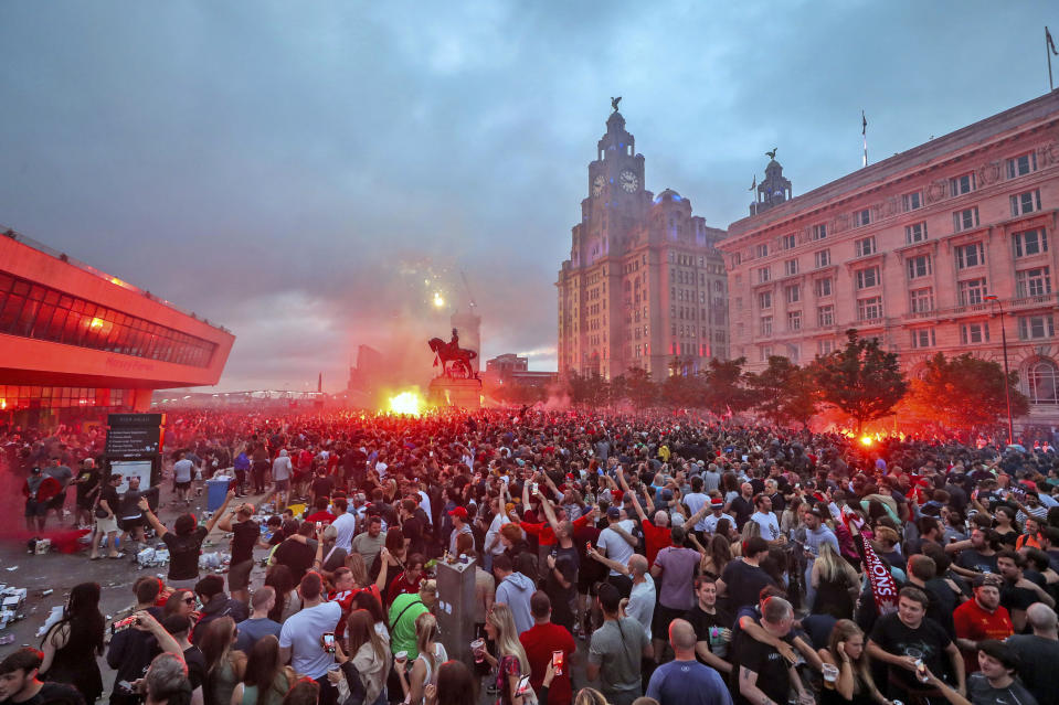 Liverpool fans let off flares outside the Liver Building in Liverpool, Friday June 26, 2020, as Liverpool soccer fans gather and celebrate for the team clinched the English Premier League title. (Peter Byrne/PA via AP)