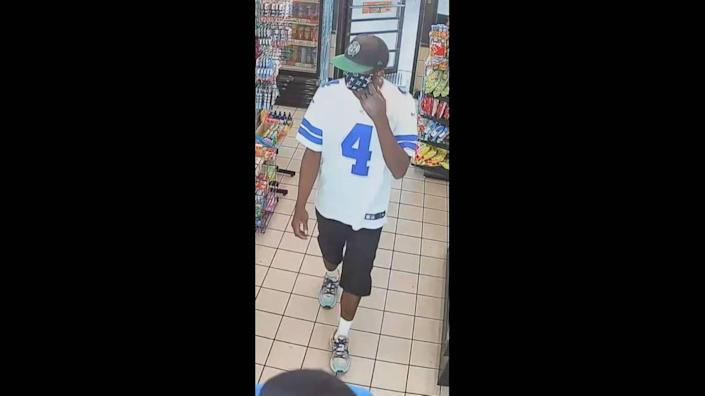 The second suspect, wearing a white Dallas Cowboys jersey, stole money from the counting machine behind the counter.
