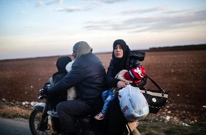 A family leaves on a motorbike as Syrians flee the embattled northern city of Aleppo wait on February 5, 2016 (AFP Photo/Bulent Kilic)