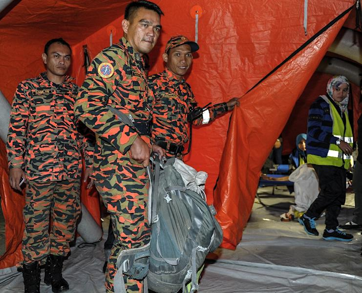 A Malaysian soldier carries victims body parts inside a rucksack, a day after a powerful earthquake Mount Kinabalu, on June 6, 2015 (AFP Photo/Mohd Rasfan)