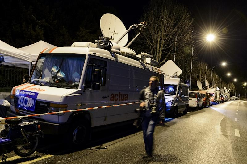A press photographer walks along news television vehicles parked in front of the hotel Beau-Rivage Palace during Iran nuclear talks in Lausanne late on March 31, 2015 (AFP Photo/Fabrice Coffrini)