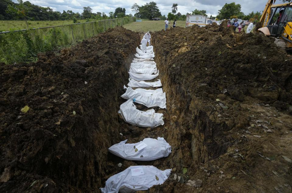 A forensics team bury a group of 15 migrants who died trying to cross the Darien Gap, at the Guayabillo cemetery in Agua Fria, Panama, Thursday, Sept. 30, 2021. The migrants, who are buried with plasticized cards containing what little information investigators were able to gather, died of natural causes or in accidental deaths while crossing the Darien jungle trying to make their way to the United States. (AP Photo/Arnulfo Franco)