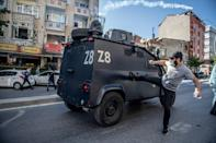 A protester aims a kick at an armoured car in Istanbul on Friday