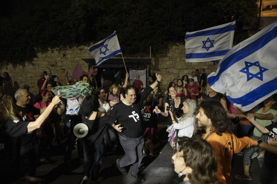 Israeli protesters dance and cheer during a demonstration against Israeli Prime Minister Benjamin Netanyahu outside his official residence in Jerusalem, Saturday, June 12, 2021. If all goes according to plan, Israel will swear in a new government on Sunday, ending Prime Minister Benjamin Netanyahu's record 12-year rule and a political crisis that inflicted four elections on the country in less than two years. (AP Photo/Ariel Schalit)