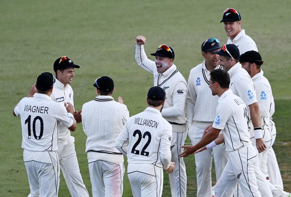 Mitchell Santner, second left, is surrounded by teammates after dismissing Pakistan captain Mohammad Rizwan with a direct throw during play on day three of the first cricket test between Pakistan and New Zealand at Bay Oval, Mount Maunganui, New Zealand, Monday, Dec. 28, 2020. (Andrew Cornaga/Photosport via AP)