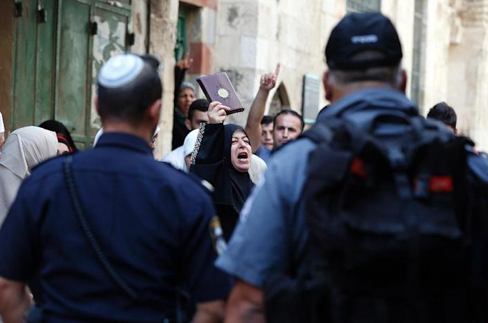 A Palestinian woman from the so-called Murabitat group holds a copy of the Koran during a protest against Jewish groups visiting the Al-Aqsa mosque compound in Jerusalem's Old City on September 16, 2015 (AFP Photo/Ahmad Gharabli)