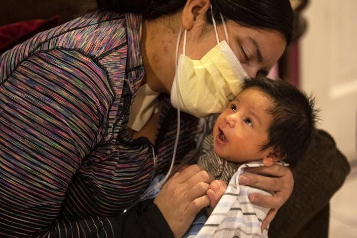 A woman in a mask holds her newborn son