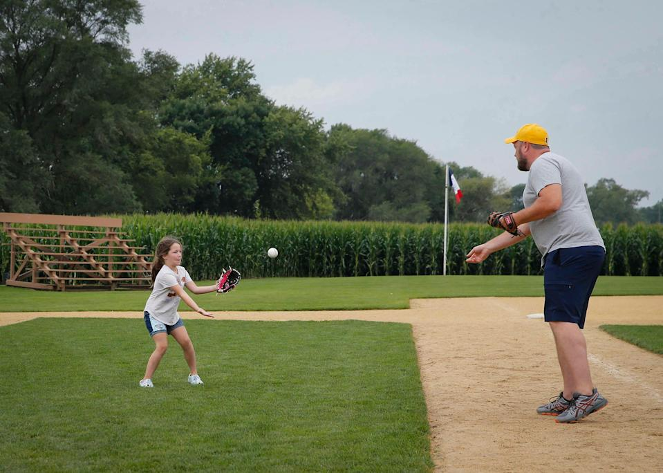 Eric Suiter of Bellevue plays catch with his daughter, Clara, 6, at the Field of Dreams on Thursday, Aug. 5, 2021, in Dyersville. The field and movie site have seen increased popularity in recent weeks due to an upcoming Major League Baseball game between the Chicago White Sox and the New York Yankees.