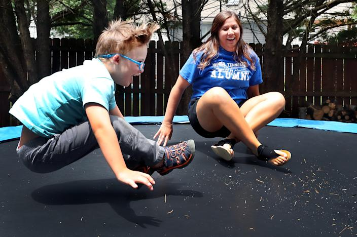 Missy Wood, right and Eli Kellum, 7, one of the three boys that she babysits, jump on a trampoline in the Kellum backyard in Murfreesboro, on Thursday, June 18, 2020.