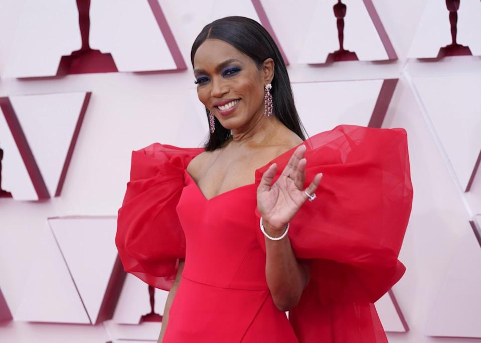 Angela Bassett wears a red dress with poufy sleeves