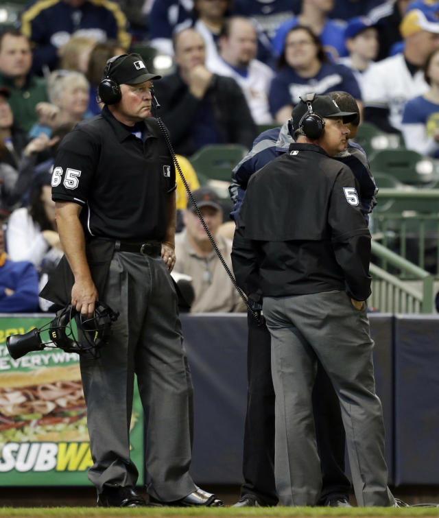 Umpire Ted Barrett (65) listens to the central replay booth in New York in the sixth inning of an opening day baseball game between the Atlanta Braves and Milwaukee Brewers, Monday, March 31, 2014, in Milwaukee. An umpire's call has been overturned for the first time under Major League Baseball's expanded replay system, with Brewers' Ryan Braun ruled out instead of safe. (AP Photo/Jeffrey Phelps)