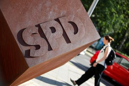 FILE PHOTO: Person walks past the logo of Germany's SPD at the party's headquarters in Berlin