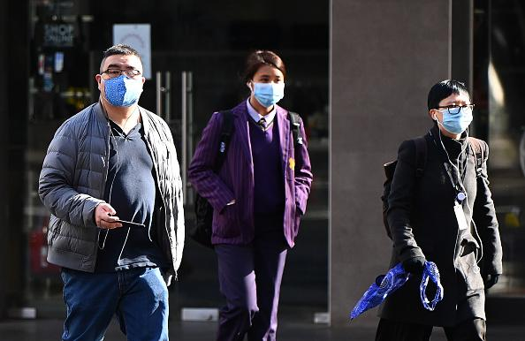 People wearing face masks walk through the city on July in Melbourne, Australia.