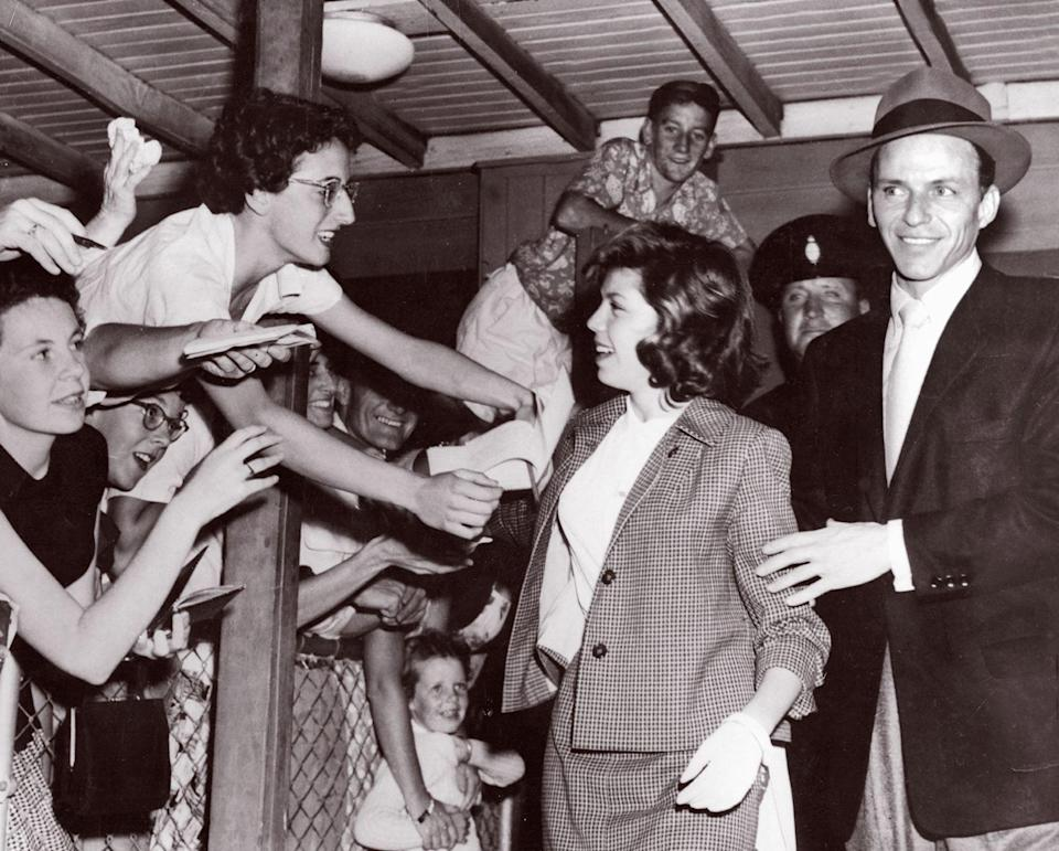 Eager fans almost spill over the fence in their efforts to get autographs from Nancy and her father, Frank Sinatra (1955)AFP via Getty