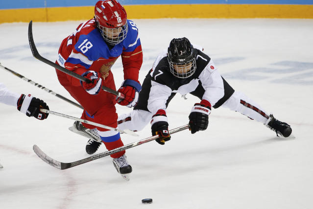 Olga Sosina of Russia and Mika Hori of Japan battle for control of the puck during the 2014 Winter Olympics women's ice hockey game at Shayba Arena Sunday, Feb. 16, 2014, in Sochi, Russia. (AP Photo/Petr David Josek)