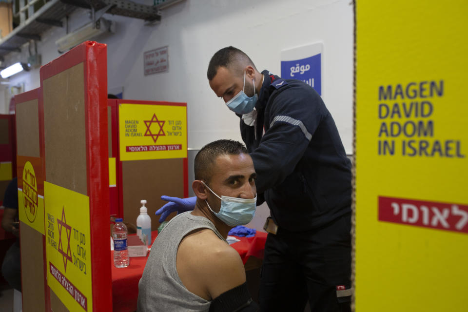 A Palestinian worker receives the Moderna coronavirus vaccine at the Hashmonim checkpoint between the West Bank and Israel, near the Israeli West Bank settlement of Nili, Monday, March 8, 2021. After delays, Israel started vaccinating Palestinians who work inside the country and its West Bank settlements on Monday, more than two months after launching an immunization blitz of its own population. (AP Photo/Maya Alleruzzo)