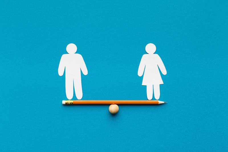 Gender equality in corporate world. Figures of man and woman on pencil seesaw, blue background, copy space (Photo: Milkos via Getty Images)