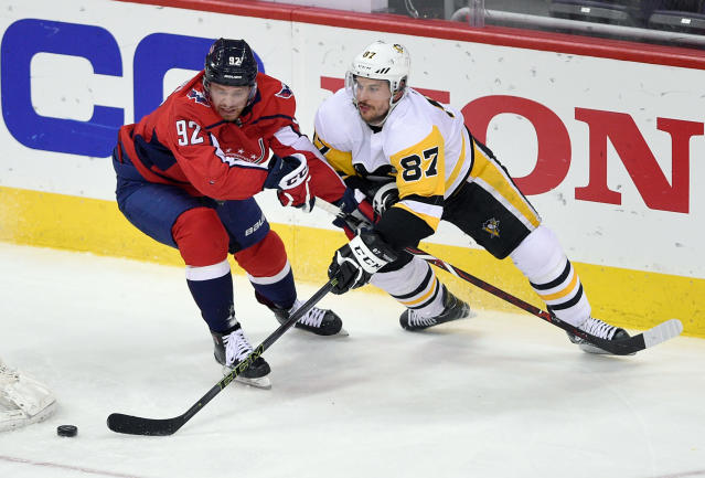 Pittsburgh Penguins center Sidney Crosby (87) skates with the puck against Washington Capitals center Evgeny Kuznetsov (92), of Russia, during the third period in Game 2 of an NHL second-round hockey playoff series, Sunday, April 29, 2018, in Washington. (AP Photo/Nick Wass)
