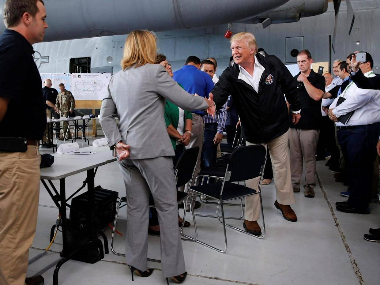 Carmen Yulin Cruz shakes hands with a humbled US President Donald Trump after he criticised her leadership in the the aftermath of Hurricane Maria (Jonathan Ernst/Reuters)