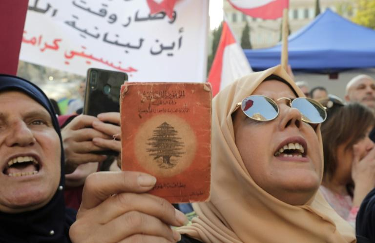 "A Lebanese demonstrator holds up an old identity card during a march organised by the ""My Nationality, My Dignity"" campaign in Beirut"