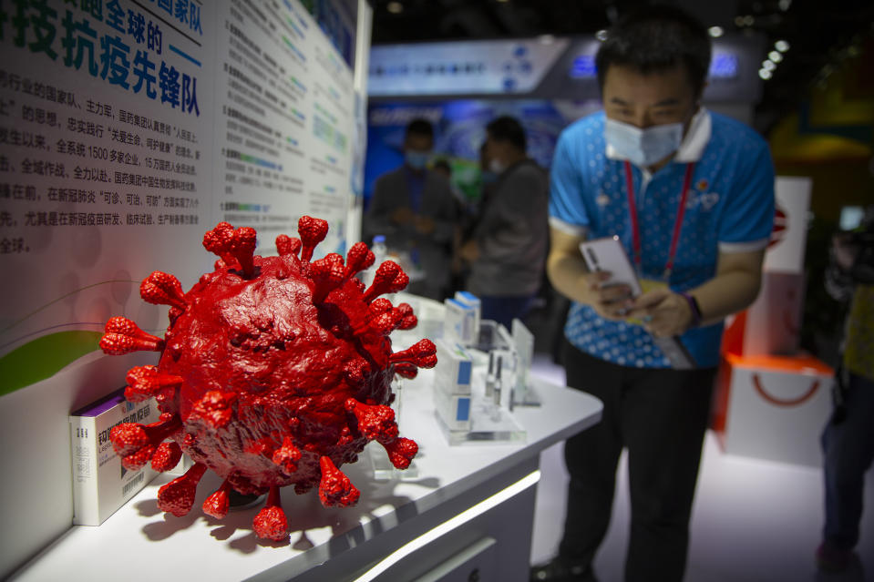 A visitor wearing a face mask takes a photo of a model of a coronavirus and boxes for COVID-19 vaccines at a display by Chinese pharmaceutical firm Sinopharm at the China International Fair for Trade in Services (CIFTIS) in Beijing, Saturday, Sept. 5, 2020. With the COVID-19 pandemic largely under control, China's capital on Saturday kicked off one of the first large-scale public events since the start of the coronavirus outbreak, as tens of thousands of attendees were expected to visit displays from nearly 2,000 Chinese and foreign companies showcasing their products and services. (AP Photo/Mark Schiefelbein)