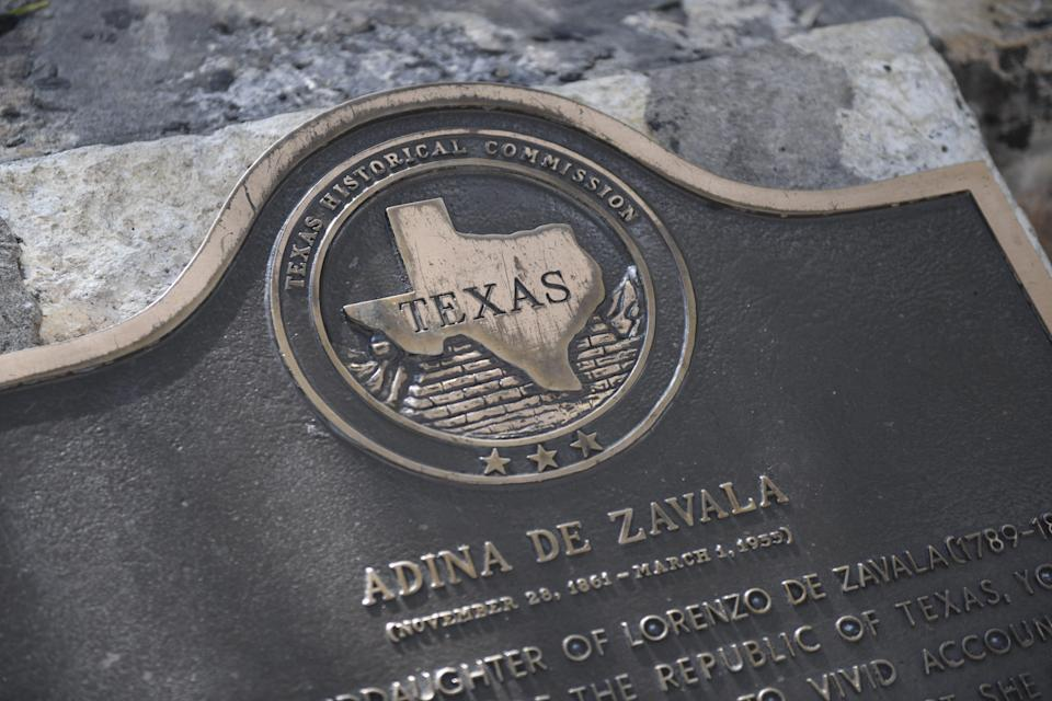 A Texas Historical Commission plaque inscribed with Adina De Zavala's biography sits in front of the Alamo.