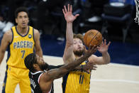 Los Angeles Clippers' Paul George (13) puts up a shot against Indiana Pacers' Domantas Sabonis (11) during the first half of an NBA basketball game, Tuesday, April 13, 2021, in Indianapolis. (AP Photo/Darron Cummings)