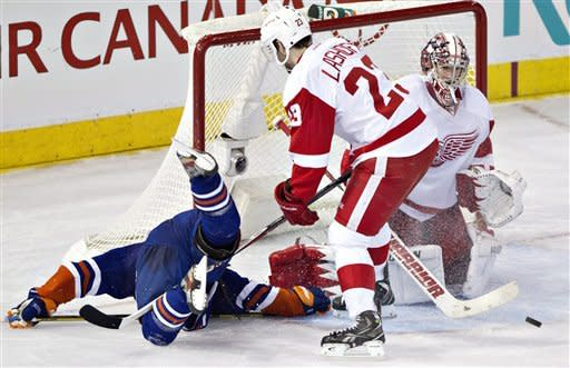 Detroit Red Wings goalie Jimmy Howard (35) makes the save as Brian Lashoff (23) trips up Edmonton Oilers Jordan Eberle (14) during third period NHL hockey action in Edmonton, Alberta, on Friday March 15, 2013. Detroit won in overtime 3-2. (AP Photo/The Canadian Press, Jason Franson)