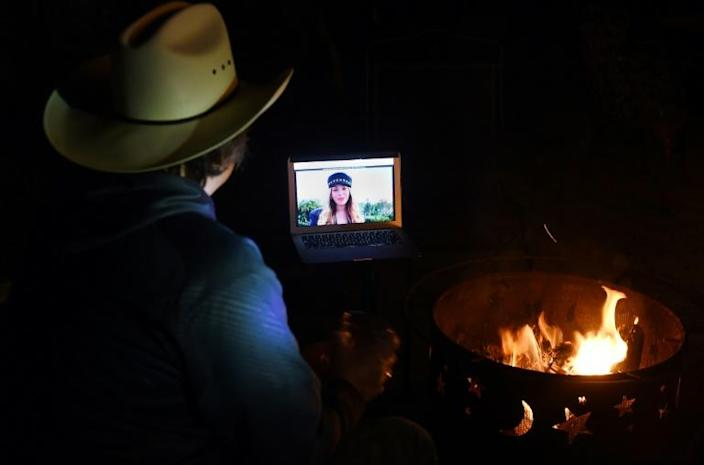 """Neighbors in Virginia gather around a fire pit to watch Beyonce speak during the """"One World: Together at Home"""" concert that also featured performances from The Rolling Stones and Taylor Swift (AFP Photo/Olivier DOULIERY)"""