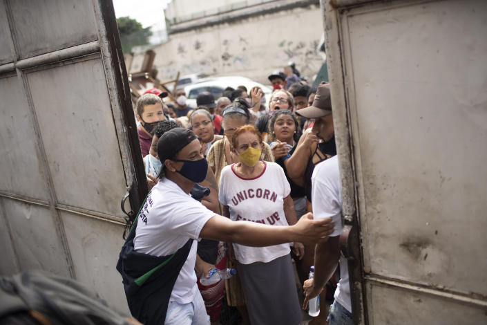 FILE - In this May 13, 2021 file photo, residents gather outside a gate for donated food from the Central Union of the Slums, known by its acronym CUFA, in the Jacarezinho favela of Rio de Janeiro, Brazil, amid the COVID-19 pandemic. As Brazil hurtles toward an official COVID-19 death toll of 500,000, President Jair Bolsonaro has waged a campaign to downplay the virus's seriousness and keep the economy humming. (AP Photo/Silvia Izquierdo, File)
