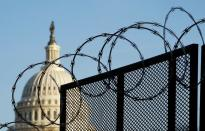 The dome of the U.S. Capitol seen behind barbed wire in Washington