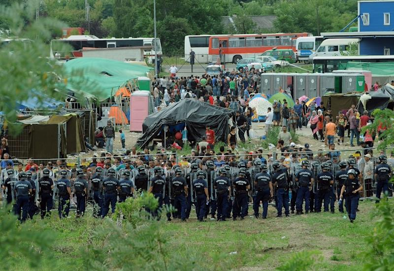 Police officers guarding a local refugee camp in the village of Roszke at the Serbian-Hungarian border on September 4, 2015 where migrants were being held
