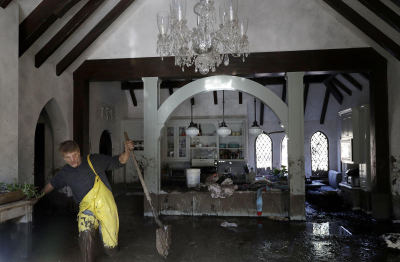Bill Asher walks through mud in his home damaged by storms in Montecito, Calif., Thursday, Jan. 11, 2018. Rescue workers slogged through knee-deep ooze and used long poles to probe for bodies Thursday as the search dragged on for victims of the mudslides that slammed this wealthy coastal town. (AP Photo/Marcio Jose Sanchez)