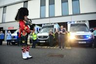 """NHS staff members and a bagpiper take part in a national """"clap for carers"""" to show thanks for the work of Britain's National Health Service in Glasgow"""