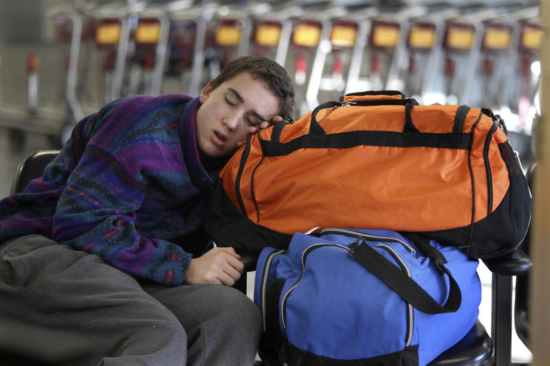 Elliott Levey, 16, of Hudson, Wis., sleeps as he waits with his father Richard and sister Avalon Levey, 18, Dec. 27, 2010 in Bloomington, Minn. .  They were trying to get to Peru via Newark, NJ. (AP Photo/Star Tribune, Elizabeth Flores)