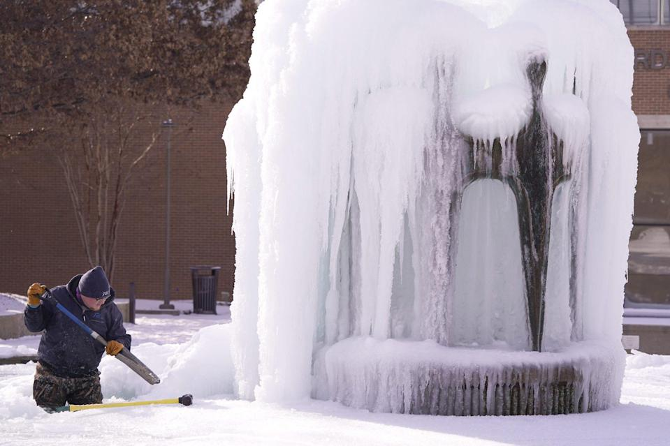 <p>City of Richardson worker Kaleb Love works to clear ice from a fountain in Richardson, Texas, on Feb. 16. </p>