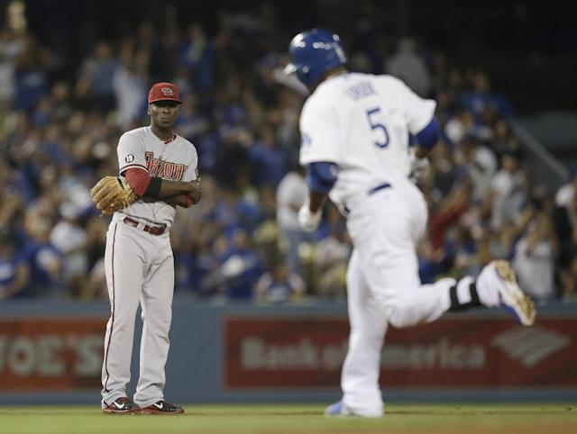 Arizona Diamondbacks shortstop Didi Gregorius, left, watches Los Angeles Dodgers' Juan Uribe round the bases after hitting his third solo home run of the game during the fifth inning a baseball game on Monday, Sept. 9, 2013, in Los Angeles. (AP Photo/Jae C. Hong)