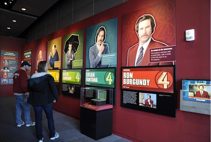 """Visitors to the Newseum view the """"Anchorman"""" movie exhibit at the Newseum in Washington, Friday, Nov. 15, 2013. The museum about news and the First Amendment has opened """"Anchorman: The Exhibit,"""" featuring costumes and props from Will Ferrell's 2004 movie """"Anchorman: The Legend of Ron Burgundy."""" The story of a fictional news team's sexist reaction to the arrival of an ambitious female reporter was a parody of real tumult in the 1970s TV business. (AP Photo/Susan Walsh)"""