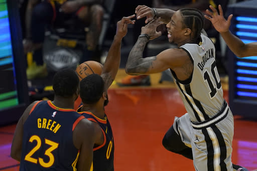 San Antonio Spurs forward DeMar DeRozan (10) loses the ball while defended by Golden State Warriors guard Brad Wanamaker, middle, and forward Draymond Green (23) during the first half of an NBA basketball game in San Francisco, Wednesday, Jan. 20, 2021. (AP Photo/Jeff Chiu)