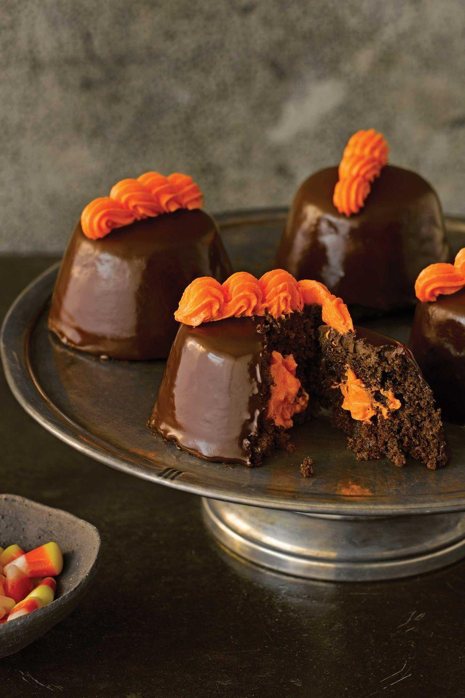 """<p>Orange food coloring, added one drop at a time, gives the cream that tops these bite-size snacks its brilliant hue.</p><p><strong>Recipes: </strong><strong><a href=""""https://www.countryliving.com/food-drinks/recipes/a2422/classic-chocolate-cake/"""" rel=""""nofollow noopener"""" target=""""_blank"""" data-ylk=""""slk:Classic Chocolate Cake"""" class=""""link rapid-noclick-resp"""">Classic Chocolate Cake</a> and </strong><a href=""""https://www.countryliving.com/food-drinks/recipes/a2428/vanilla-cream-filling/"""" rel=""""nofollow noopener"""" target=""""_blank"""" data-ylk=""""slk:Vanilla Cream Filling"""" class=""""link rapid-noclick-resp""""><strong>Vanilla Cream Filling</strong></a></p>"""