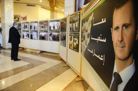 """A picture of Syria's President Bashar al-Assad (R) is seen during the """"Syria, on the outskirts of Dawn"""" photo exhibition, marking the fourth anniversary of the Syrian crisis, at the Opera house in Damascus March 15, 2015. REUTERS/Omar Sanadiki"""