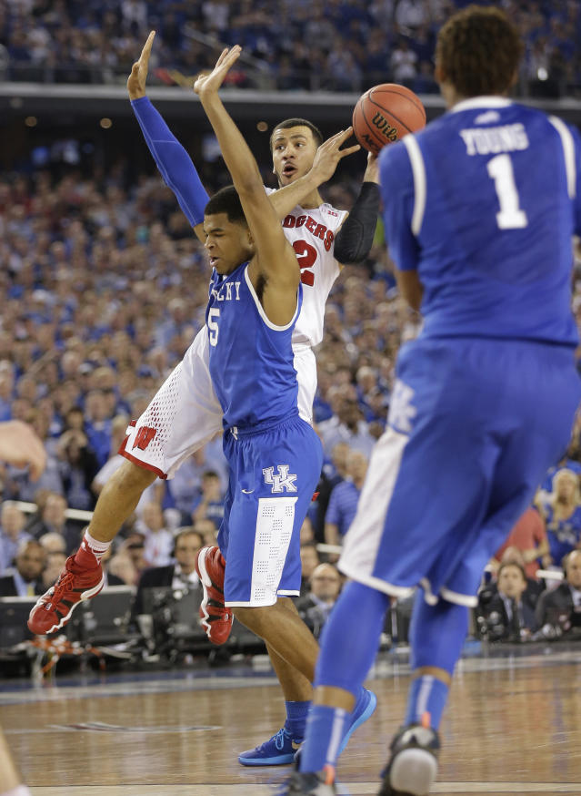 Wisconsin guard Traevon Jackson (12) is fouled by Kentucky guard Andrew Harrison (5) during the final seconds of their NCAA Final Four tournament college basketball semifinal game Saturday, April 5, 2014, in Arlington, Texas. (AP Photo/Eric Gay)
