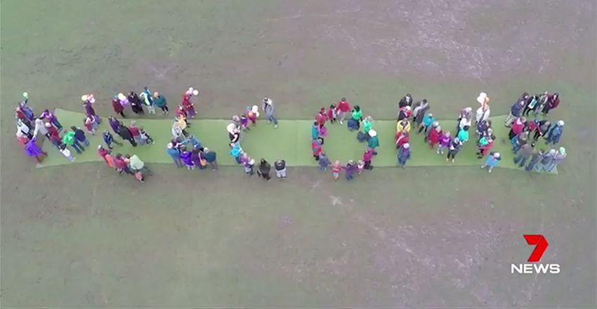 Supporters of refugees moving into the facility spell out the word 'welcome'. Image: 7News