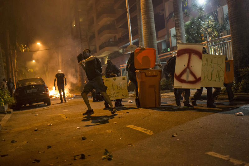 A protester throws an object at police as others take cover behind a trash bin and signs as they protest outside the Guanabara Palace where the state governor has his office in Rio de Janeiro, Brazil, Thursday, July 11, 2013. Workers across Brazil walked off their jobs in a nationwide strike demanding better working conditions and improved public services in Latin America's biggest nation. (AP Photo/Felipe Dana)