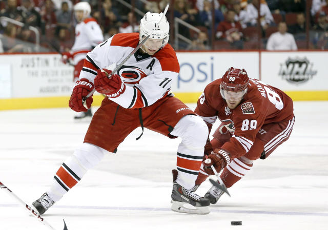 Carolina Hurricanes' Jordan Staal (11) battles Phoenix Coyotes' Mikkel Boedker (89), of Denmark, for the puck during the first period of an NHL hockey game, Saturday, Dec. 14, 2013, in Glendale, Ariz. (AP Photo/Ross D. Franklin)