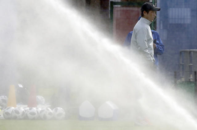 Japan's head coach Akira Nishino stands near water sprinkling prior to a training session of Japan national soccer team at the 2018 soccer World Cup in Kazan, Russia, Thursday, June 14, 2018. (AP Photo/Eugene Hoshiko)