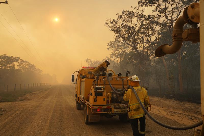 Pictured is a firefighter next to a tanker in the Queensland bushfires.