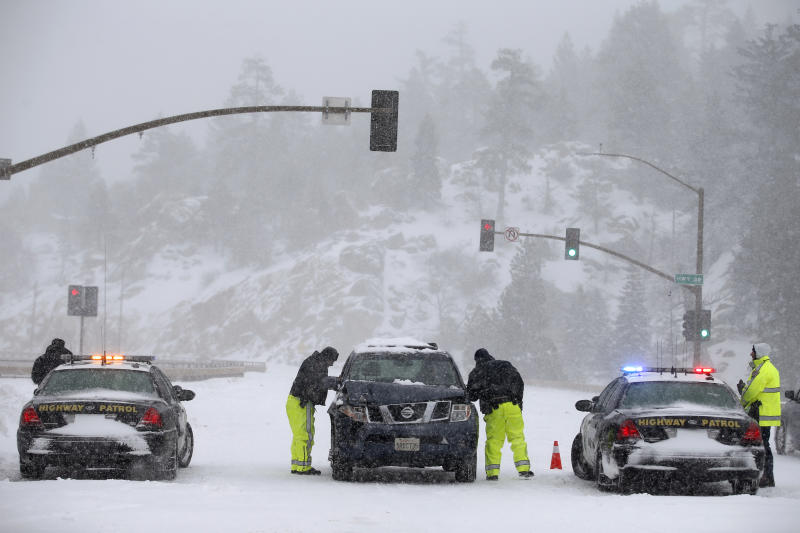 California Highway Patrol officers search a vehicle for former Los Angeles police officer Christopher Dorner at a checkpoint near Big Bear Lake, Calif, Friday, Feb. 8, 2013. Law enforcement officers working in falling snow searched the Southern California mountain for Dorner, who is accused of carrying out a killing spree because he felt he was unfairly fired from his job. (AP Photo/Jae C. Hong)